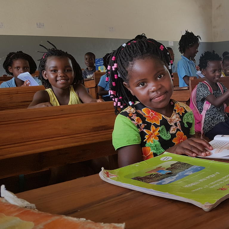 Girls sit at desks in a classroom in Mozambique