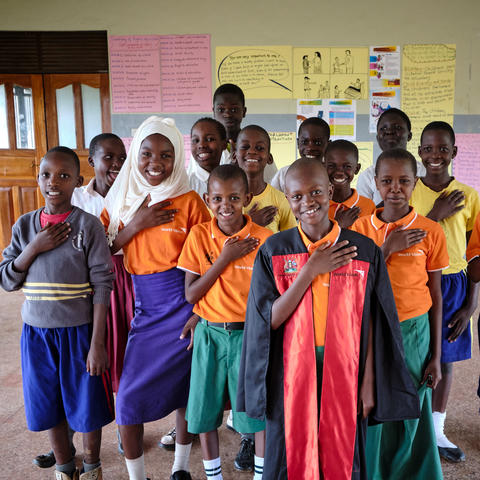 A group of African children stand together with their hands on their hearts