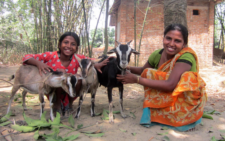 Golapi and her daughter smiling holding gift goats