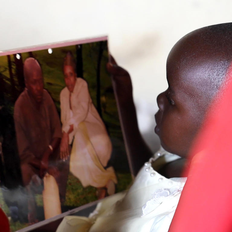 A girl looks at a photo of her parents