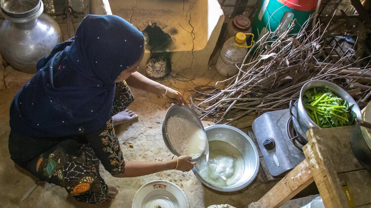 Khadiza, preparing a lunch of rice and bottle gourds for her children back in their shelter.