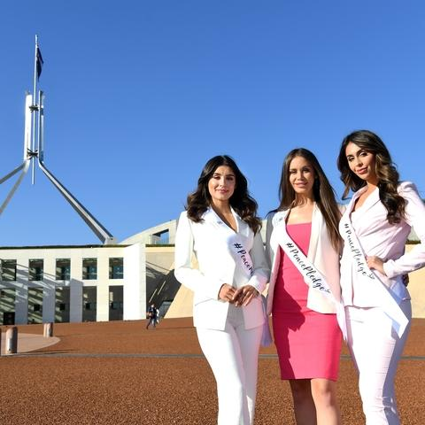 Three Miss World Contestants stand in front of Parliament House.