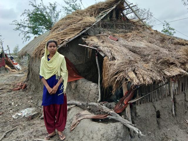 A teenage girl wrapped in a yellow head scarf stands in front of her small mudbrick home damaged by a cyclone in India.