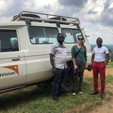 Three people standing in front of a four wheel drive.