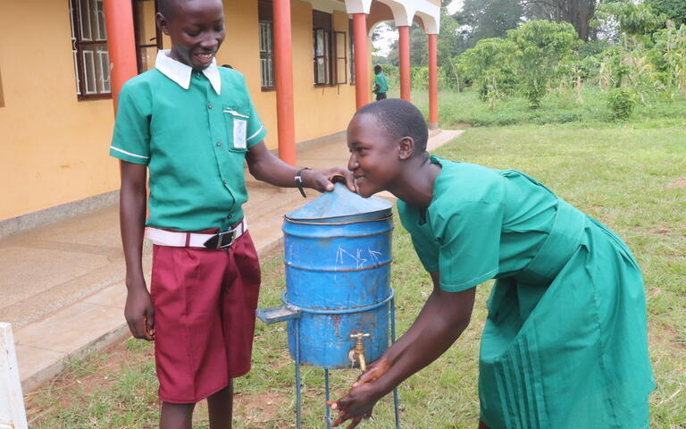 Ugandan children with access to education and clean water