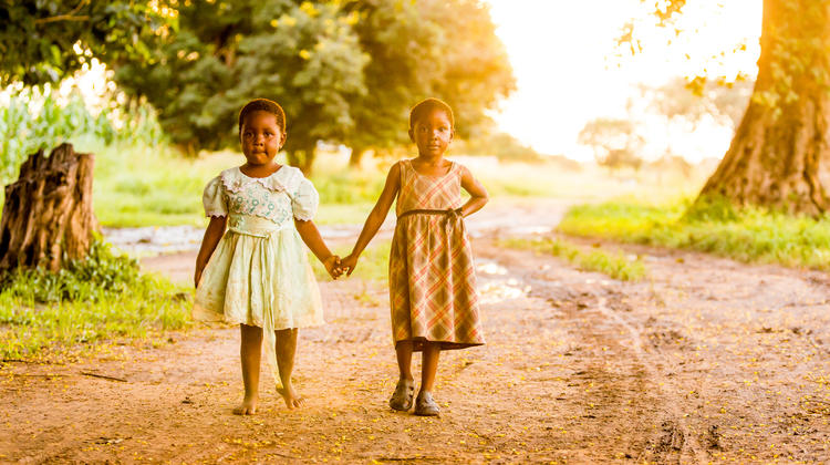 Barbara and Lulu, both four-years-old, walk home from school together at sunset.